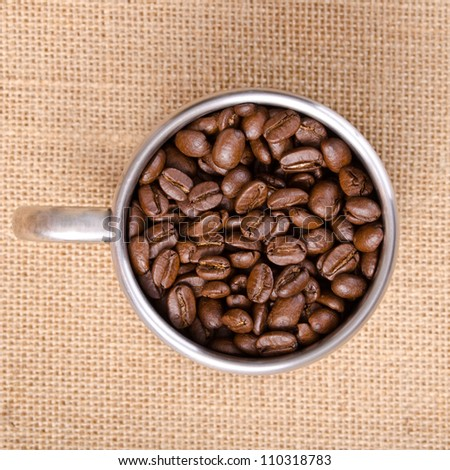 Coffee Bean in Stainless Cup on Natural Sack Background - Top View