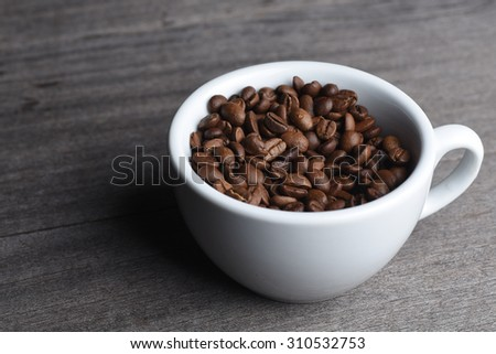 Coffee Bean in White Cup on Wooden Table