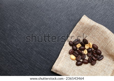 Coffee bean put on the coffee bean sack in the scene appear the back color leather background. - stock photo