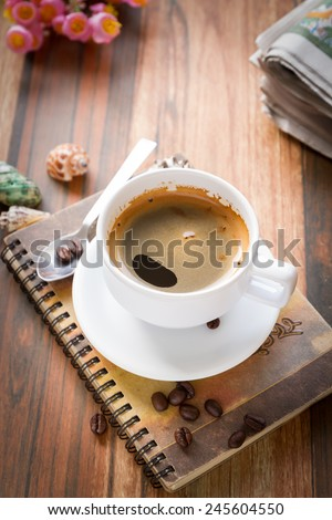 Coffee bean with cup coffee and notebook on old wooden table vintage color toned - stock photo