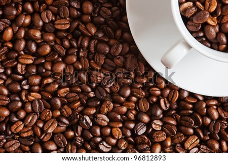 coffee beans and a cup filled with them