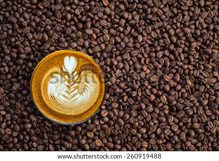 Coffee beans and a cup of coffee with beautiful Latte art - stock photo