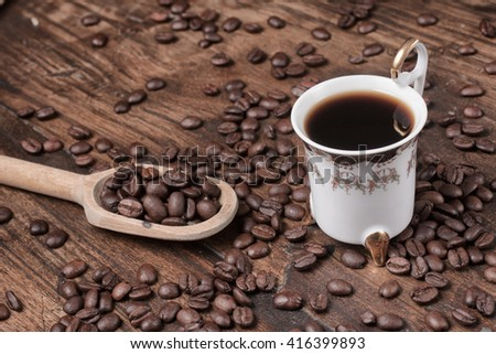 Coffee Beans and a old cup over a wooden table