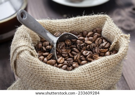 coffee beans and a silver shovel lying in a sack - stock photo