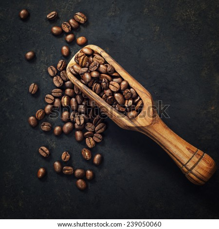 Coffee beans and an old wooden scoop on dark background - stock photo