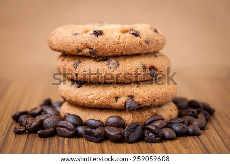 Coffee beans and chocolate chip cookies on a wooden table, warm tone style - stock photo