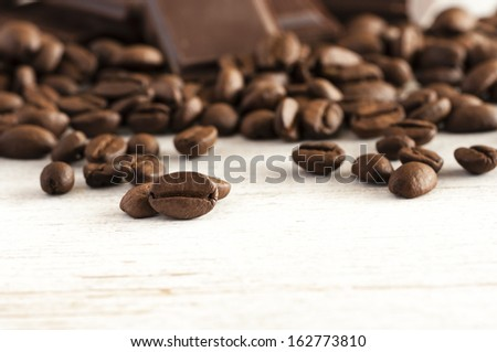 Coffee beans and chocolate pieces close up