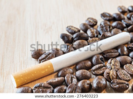Coffee beans and cigarette on wood background, selective focus  (detailed close-up shot)