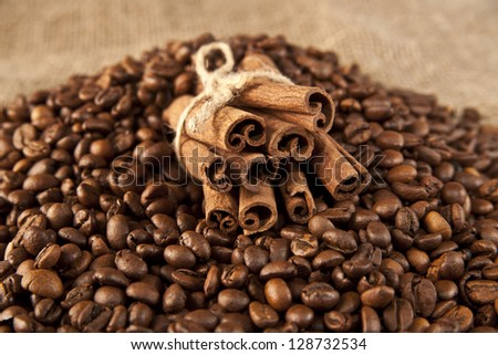 Coffee beans and cinnamon on a sacking background - stock photo