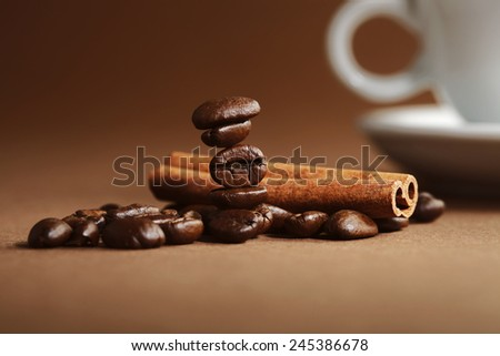Coffee beans and cinnamon on brown background - stock photo