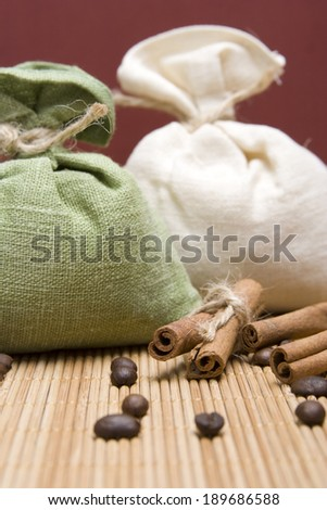 Coffee beans and cinnamon sticks in canvas sack on wooden background. Two sacks, green and white - stock photo