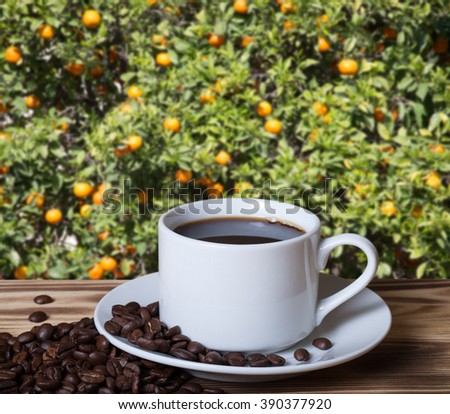 Coffee beans and coffee in white cup on wooden table opposite a defocused abstract background with orange tree branches. Collage. Selective focus. - stock photo