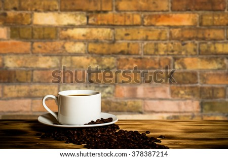 Coffee beans and coffee in white cup on wooden table opposite a defocused brick wall for background. Collage. Selective Focus. Toned. - stock photo