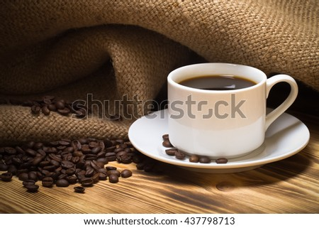 Coffee beans and coffee in white cup on wooden table with burlap. Selective focus. Toned.