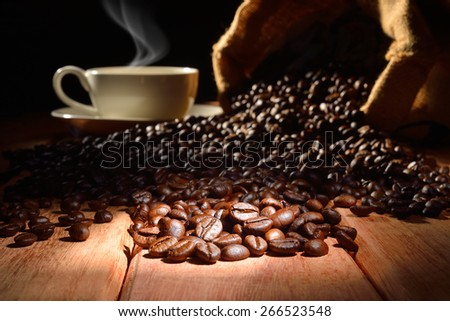 Coffee beans and cup of coffee with smoke on old wooden background  - stock photo