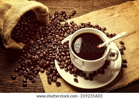 Coffee beans and cup on old wooden background vintage style