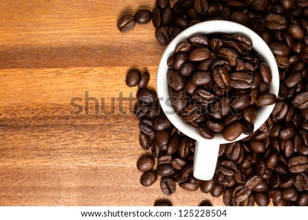coffee beans and cup on wood surface, background