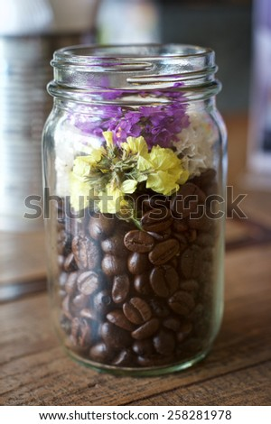 Coffee beans and flower in the Glass bottle on a wooden table - stock photo