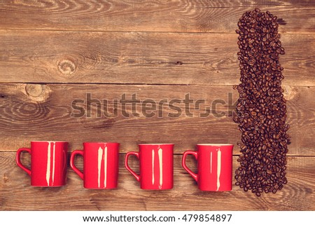 coffee beans and four red cup on wood table