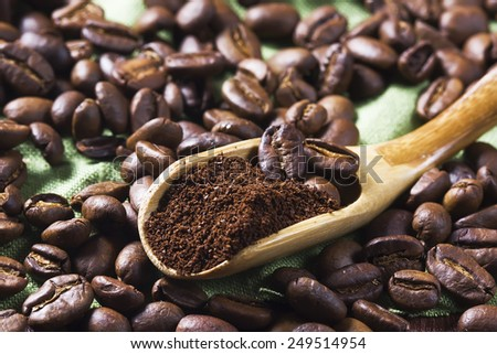 coffee beans and ground coffee in a wooden spoon. macro - stock photo