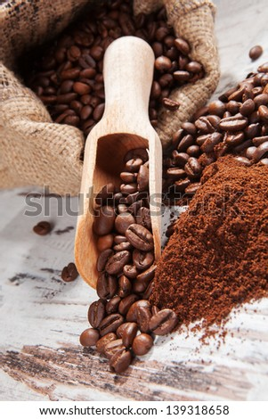 Coffee beans and ground coffee in brown sack on white wooden background. Gourmet coffee background, country style.