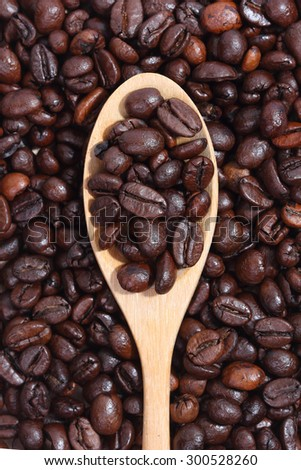 coffee beans and ground coffee in spoon on textured wood. - stock photo