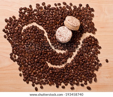 coffee beans and macaroons on wooden background - stock photo
