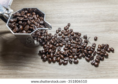 Coffee beans and Moka Pot coffee maker over wooden background. Selective focus - stock photo