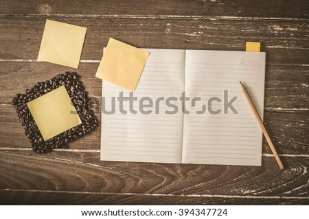 coffee beans  and  note book ?Sticky Note with pencil on the texture old wood