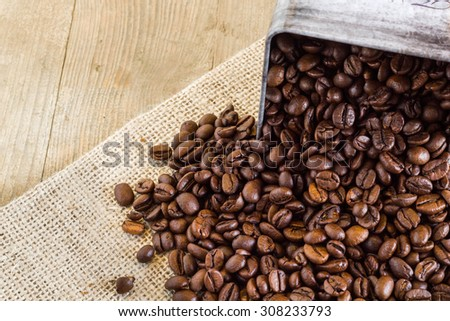 Coffee beans and old sack on a wooden table.