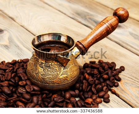 coffee beans and turk on a wooden background - stock photo