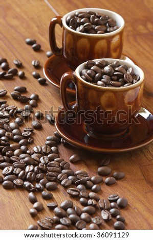 Coffee beans and two brown cups on wooden surface.