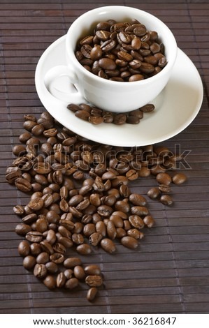 Coffee beans and white cup with saucer on brown mat.