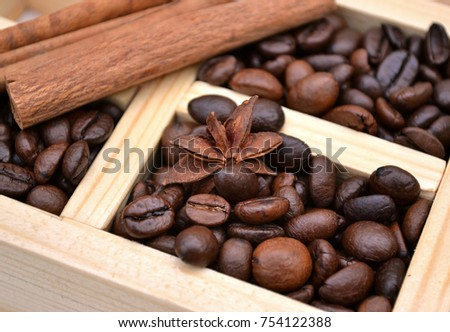 Coffee beans and winter spices are  in a  wooden box