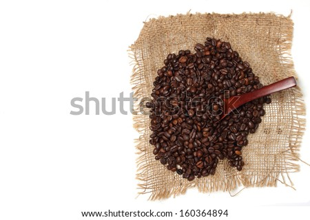 coffee beans and wood spoon on sack with white background