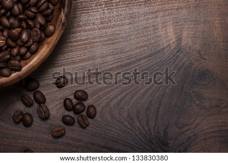 coffee beans and wooden bowl on the brown table - stock photo