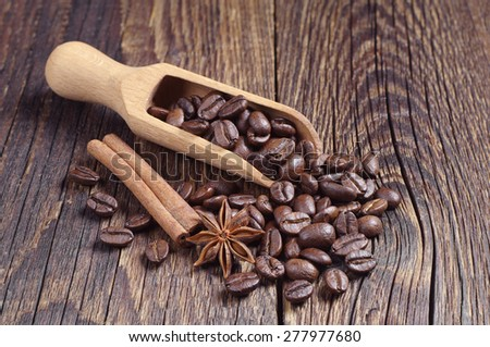 Coffee beans and wooden scoop on wooden background - stock photo