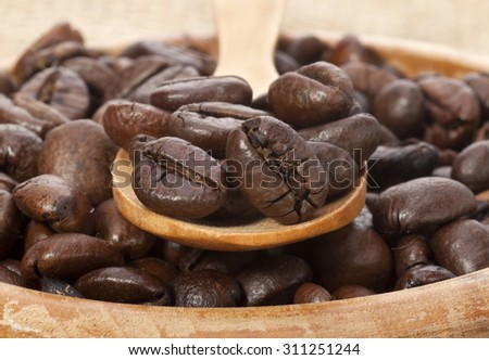 Coffee beans and wooden spoon in a wooden plate - stock photo
