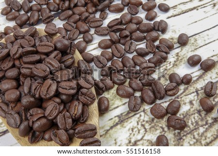 coffee beans and wooden spoon on old rusty background