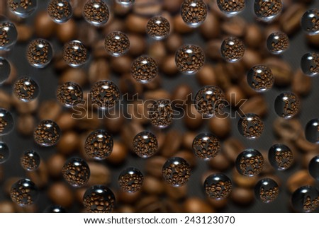 coffee beans are reflected in drops of water on a blurred background - stock photo