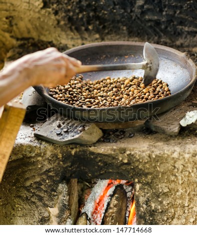 Coffee beans are roasting in pan. Traditional techniques. - stock photo