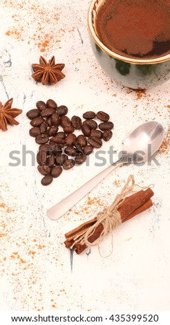 Coffee beans arranged in heart with cinnamon and anise on white wooden table. - stock photo