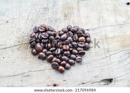 Coffee beans arranged into a shape of heart with steam on wood