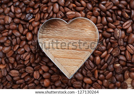 coffee beans as background from good roasted coffee beans with heart shaped metal frame - stock photo