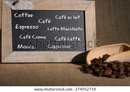 Coffee beans blackboard lying on jute fabric / Coffee beans - stock photo