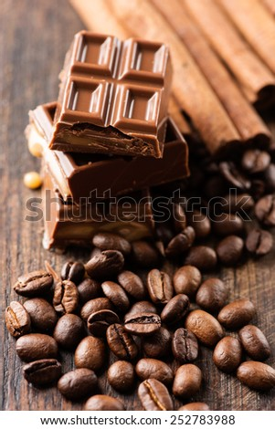 Coffee beans, chocolate candy bar and cinnamon sticks on wooden table - stock photo
