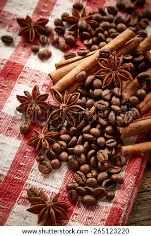 Coffee beans, cinnamon and star anise on serviette - stock photo