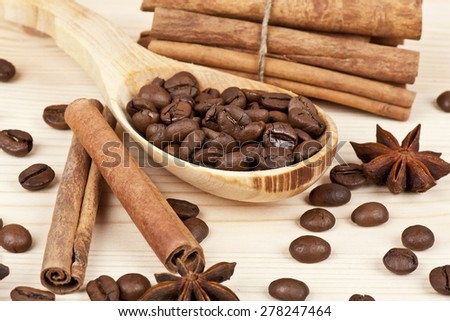 Coffee beans, cinnamon and stars of anise on a wooden background  - stock photo