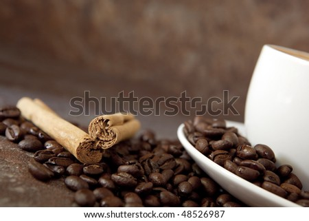 Coffee beans, cinnamon sticks, and white coffee cup, over stone background.  Angled view, soft focus. - stock photo