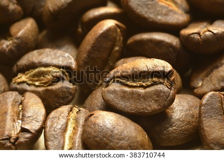 Coffee beans close up image of energy a morning pick-me-up on tan yellow